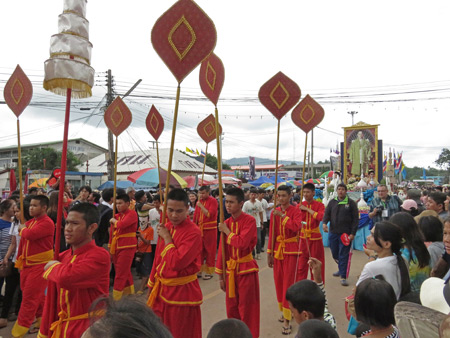 A procession of brightly clad young men walk in the parade at the Phi Ta Khon festival in Dan Sai, Thailand.