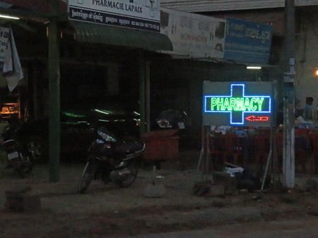 A poignant pharmacy sign glows in the gloom in Siem Reap, Cambodia.