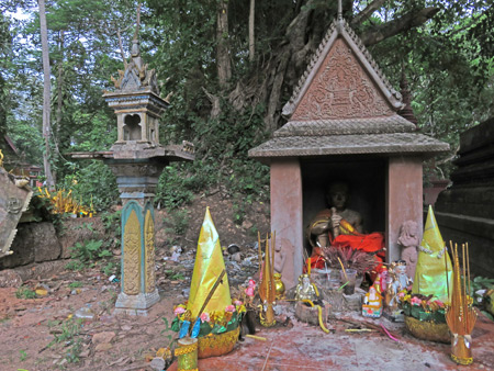 A spirit house and a Buddhist shrine at Wat Preah An Kau Sai in Siem Reap, Cambodia.