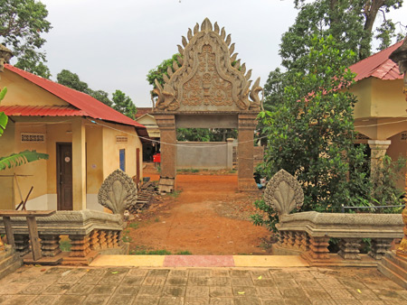 A side gate bathed in orange dirt at Wat Preah An Kau Saa in Siem Reap, Cambodia.