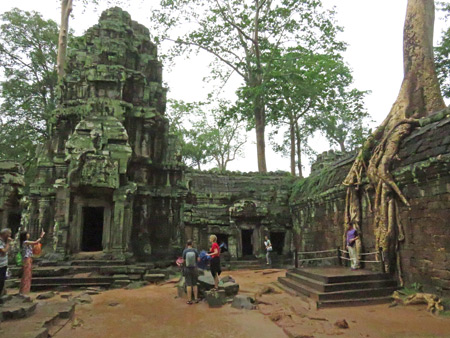 Tourists pose at Ta Prohm, Angkor in Siem Reap, Cambodia.