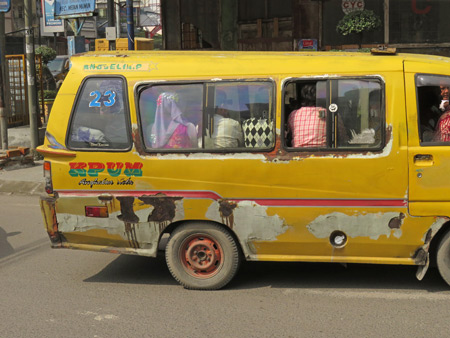 A packed mini-van in Medan, Sumatra, Indonesia.