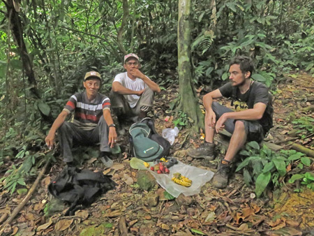 Two local Indonesian guides and Alex take a break in Bukit Lawang, Sumatra, Indonesia.