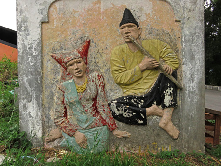 A carving of traditional Minangkabau musicians on a small booth near the entrance to Fort de Kock in Bukittinggi, Sumatra, Indonesia.