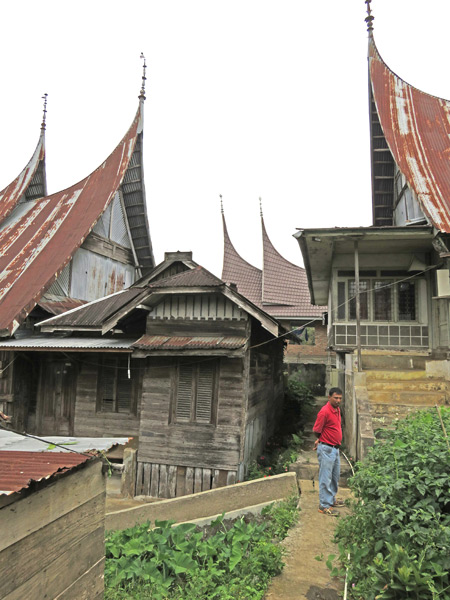 Armando stands amid the pointy rooftops of traditional Minangkabau houses in Rao Rao near Bukittinggi, Sumatra, Indonesia.