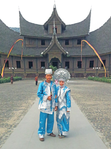 A couple tries on traditional Minangkabau costumes in front of Pagarayung Palace near Batu Sangkar, Sumatra, Indonesia.