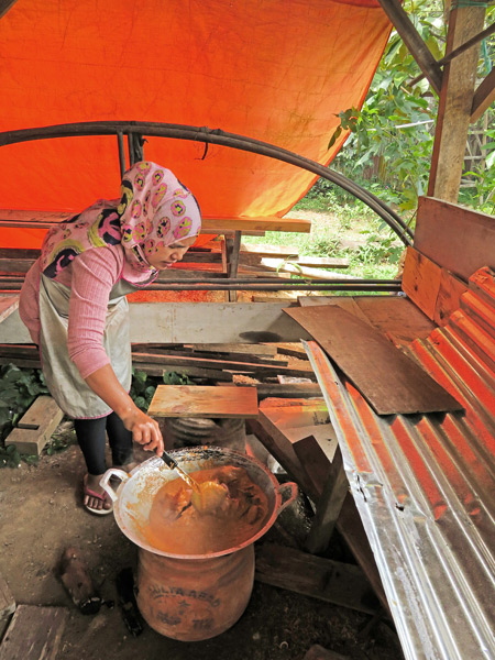 A woman cooks up something delicious in Kiniko, near Bukittinggi, Sumatra, Indonesia.