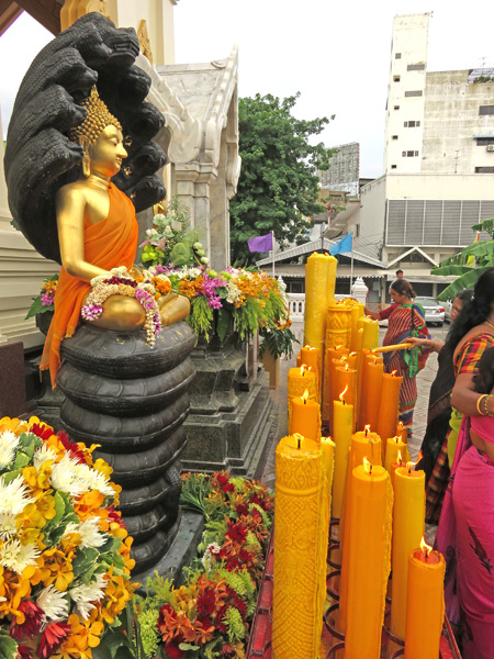 A small Buddha image and some big candles at Wat Traimit in Chinatown, Bangkok, Thailand.