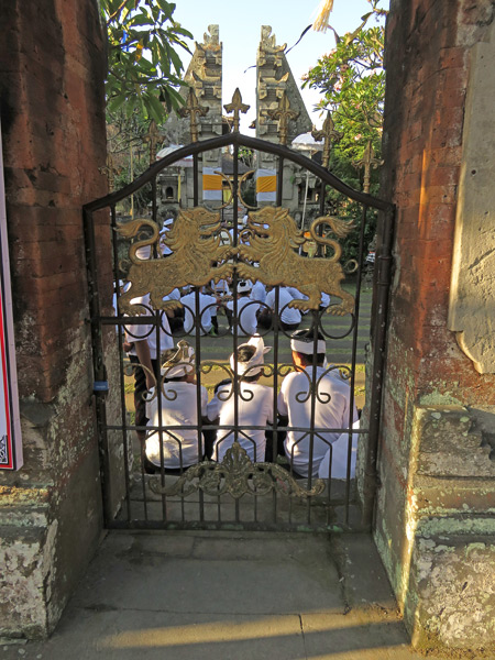 Looking through the gate at a Hindu temple ceremony at Pura Desa in Ubud, Bali, Indonesia.