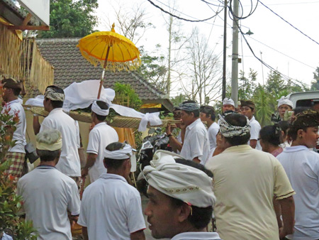 A procession of men carries a body into a small Hindu cremation ceremony in Penestanan, Ubud, Bali, Indonesia.