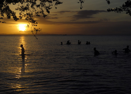 A small gathering of humans in the water of Lake Nicaragua at Punta Jesus Maria on the west side of Isla de Ometepe, Nicaragua.