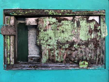 An extremely distressed window in Caye Caulker, Belize.