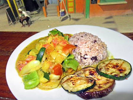 A plate of delicious yellow curry vegetables and rice overlooking Playa Asuncion in Caye Caulker, Belize.