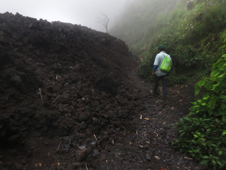Our guide, Samuel, leads us past a wall of volcanic rock at Pacaya volcano in Guatemala.