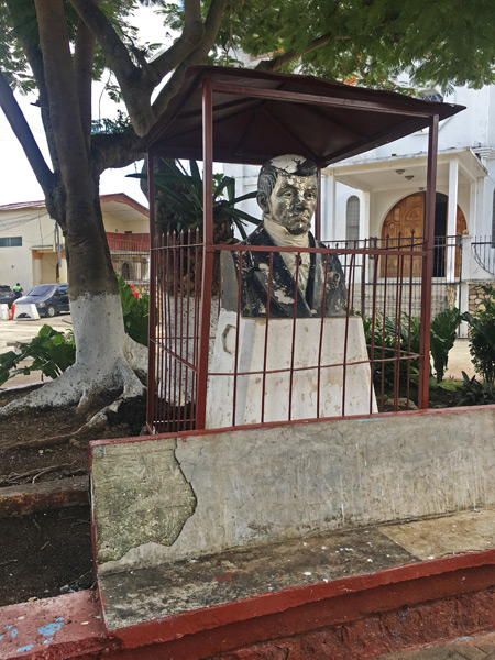 A semi-imprisoned statue at Central Park in Flores, Guatemala.
