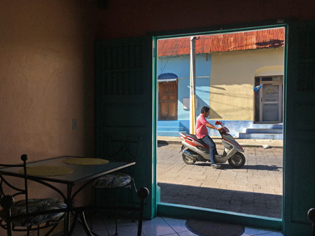 Looking out at the colorful streets from the quaint interior or Cafe Uka in Flores, Guatemala.