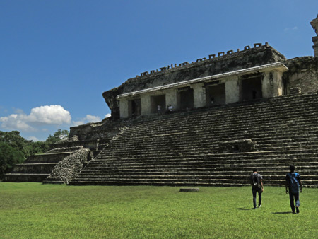 Two guys walk toward El Palacio at the Palenque Ruins, Mexico.