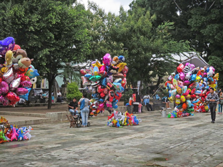 An explosion of colorful balloons in front of the Catedral de Nuestra Señora De La Asunción in Oaxaca City, Mexico.