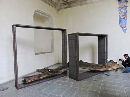 A log penetrates two boxes at the Museo de las Culturas de Oaxaca in Oaxaca City, Mexico.