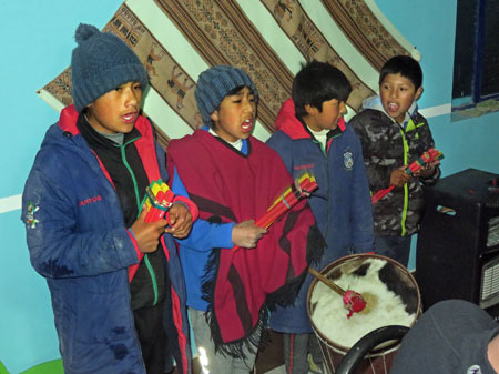 Local boys sing a few traditional Bolivian songs while playing pan pipes and a drum during dinner at a hostel in Markuu Villa Mar, Bolivia.
