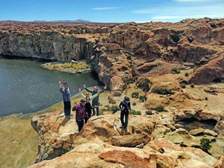 The group waves on a cliff at the beautiful Laguna Catal in the Reserva Nacional de Fauna Andina Eduardo Avaroa, Bolivia.