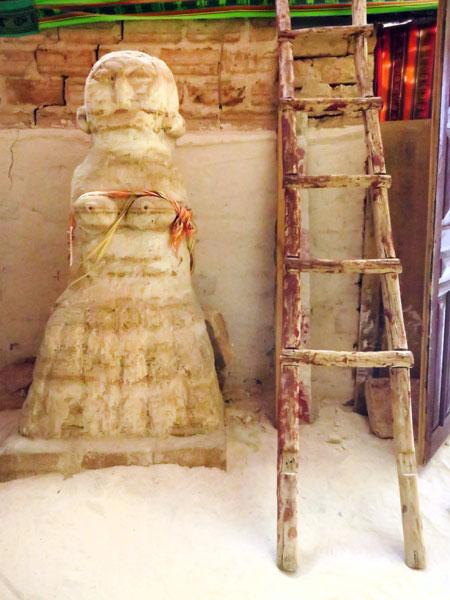 A salt statue and a rickety ladder in an old salt hostel on the Salar de Uyuni, Bolivia.
