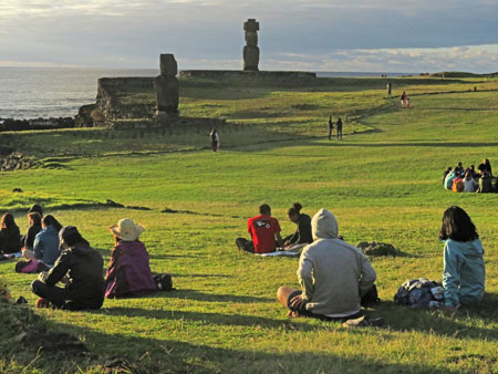 A crowd awaits sunset at Ahu Tahai, Rapa Nui, Chile.