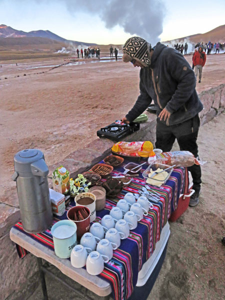 The tour guide Nicholas spins a DJ set at breakfast as steam flies out of his neck. Just kidding, he's cooking eggs. El Tatio geyser field, Andes Mountains, Chile.