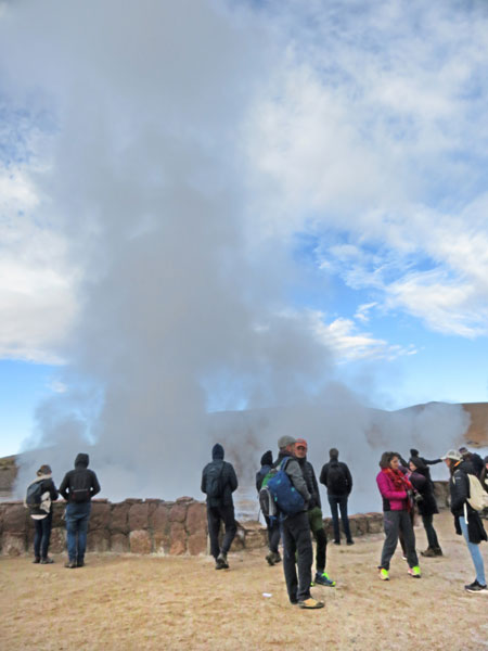 Some guys and a geyser at El Tatio geyser field, Andes Mountains, Chile.