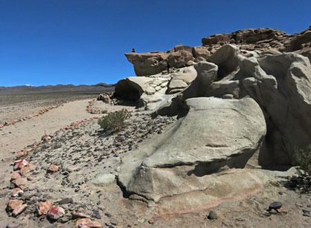 A person sits perched on an overhang in the Valle de Arcoiris, near San Pedro de Atacama, Chile.