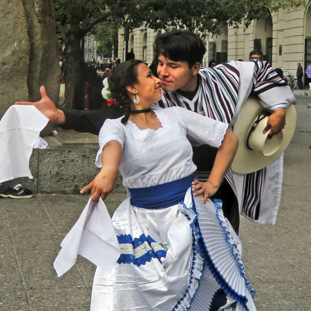 A young couple performs a traditional Cueca dance at the Plaza de Armas in Santiago, Chile.