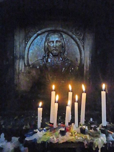 A picture of Jesus Christ with candles inside the base of the Cristo del Sagrado Corazón on the summit of Cerro Churuquella in Sucre, Bolivia.