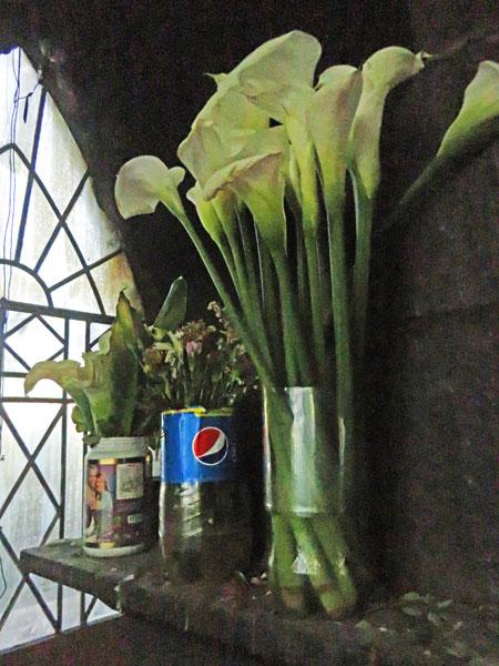 Floral arrangements in plastic bottles inside the base of the Cristo del Sagrado Corazón on the summit of Cerro Churuquella in Sucre, Bolivia.