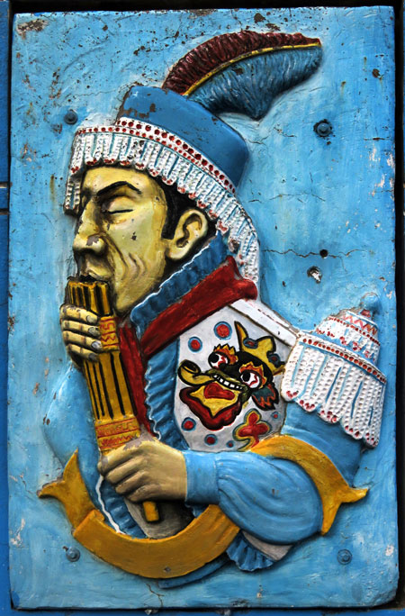 A carving of a pan pipes player on a wall in Puno, Peru.