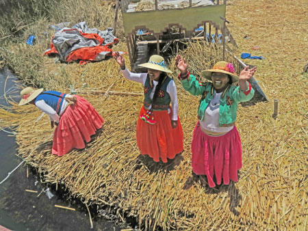 Three local women exclaim, 'Hasta la vista, baby!' as tourists leave on a boat in the Uros Islands near Puno, Peru.