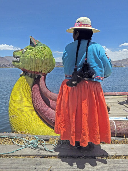 A woman stands next to a totora reed boat on the Uros Islands near Puno, Peru.