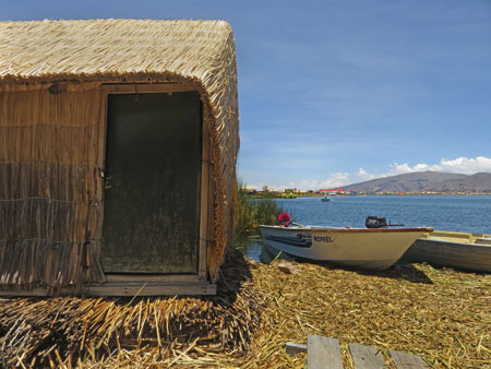 A totora reed hut and a boat on the Uros Islands near Puno, Peru.