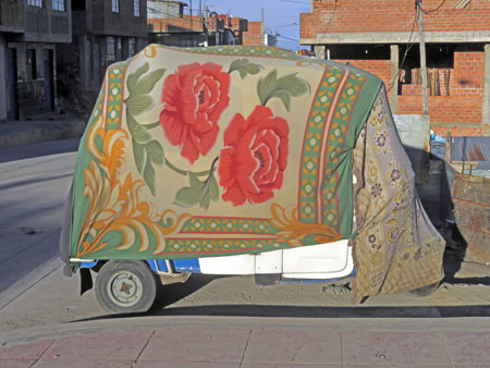 A tuk-tuk is all covered up with nowhere to go in Puno, Peru.
