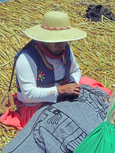 A woman sews a textile by hand on the Uros Islands near Puno, Peru.