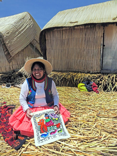 A woman holds a pillow case that I bought on the Uros Islands near Puno, Peru.