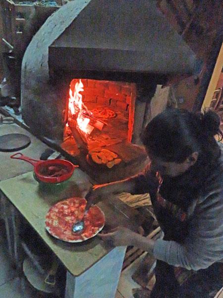 A woman prepares a pizza at Dino's in Cuzco, Peru.