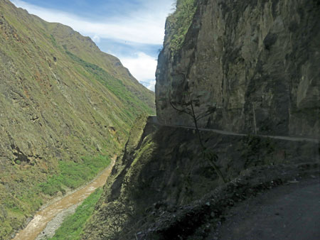 A gravel road perched precariously on a cliff near Hidroelectrica, Peru.