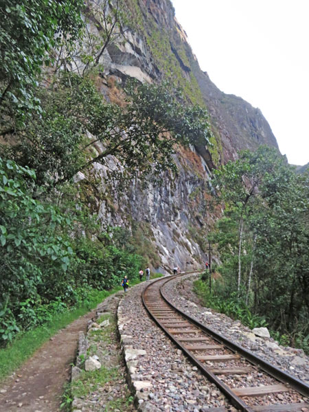 Temporary hobos walk along the train tracks in between Hidroelectrica and Aguas Calientes, Peru.
