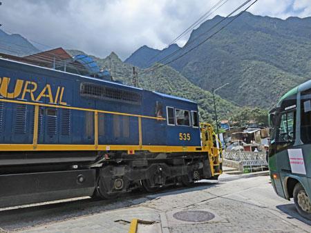 A Peru Rail locomotive crosses the street in Aguas Calientes, Peru.